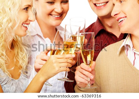 Portrait of joyful friends looking at each other with smiles during pronouncing toast