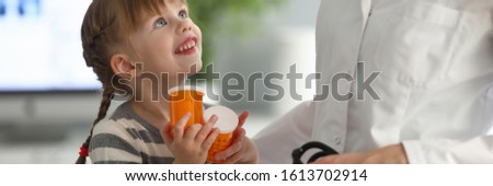 Portrait of joyful kid sitting in modern clinic office and looking at camera with joy. Professional physician holding special stethoscope and giving girl jars with medicine. Health checkup concept