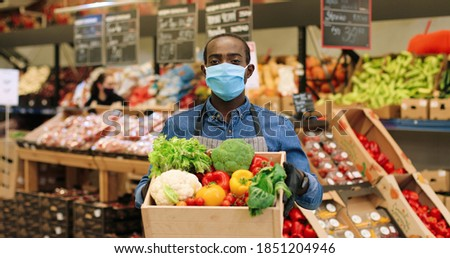 Portrait of joyful male food store manager in mask and gloves standing in supermarket and holding box with fresh vegetables, looking at camera and smiling. African American mam working at grocery. Imagine de stoc ©