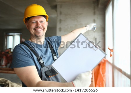Portrait of joyful man wearing protective suit holding paper folder with outlay or work plan. Smiling boy pointing at something in bright window. Building concept