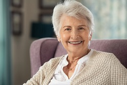Portrait of joyful old woman sitting on armchair looking at camera. Retired woman smiling while sitting alone in care centre. Portrait of an elegant senior grandmother relaxing at home with copy space