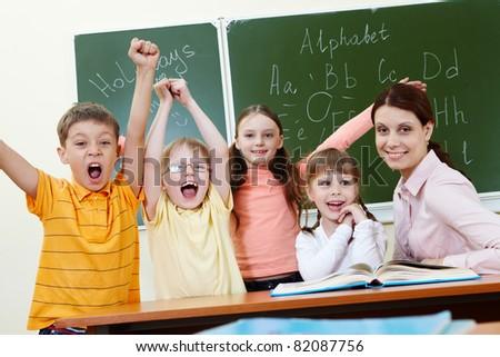 Portrait of joyful schoolchildren showing gladness with their teacher near by