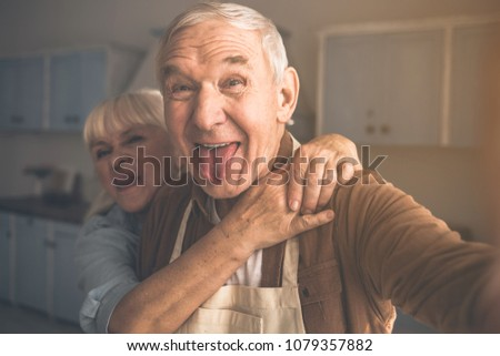 Portrait of joyful senior married couple having fun in cook room. They are taking photo of themselves and laughing while cuddling #1079357882