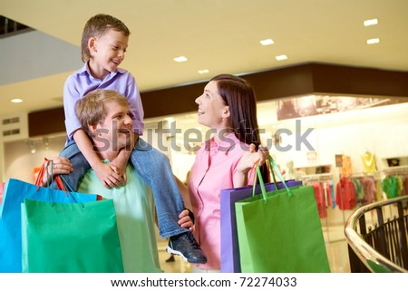 Portrait of joyful woman looking at her son on father?s shoulders in the mall