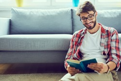 Portrait of joyful young man reading book while sitting on floor in his living room