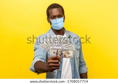 Portrait of joyous wealthy man with surgical medical mask holding out dollar bills at camera, boasting money won in lottery. indoor studio shot isolated on yellow background