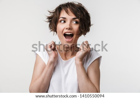 Portrait of joyous woman with short brown hair in basic t-shirt rejoicing and clenching fists isolated over white background