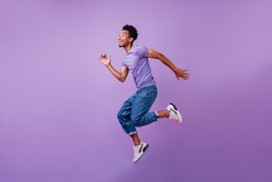 Portrait of jumping amazed guy in white sneakers. Indoor shot of dancing stylish male model in purple t-shirt.