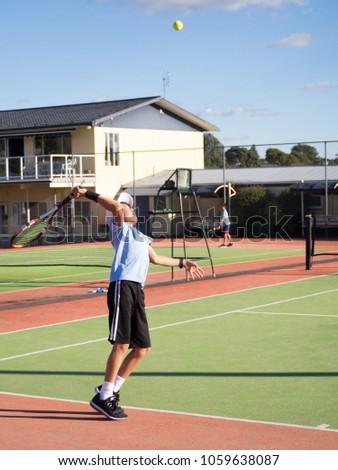 Portrait of Junior Boy Teenage Children Tennis Player Serving Ball Whilst Playing Match on Court in Summer Weather #1059638087