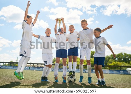 Portrait of junior football team cheering happily and jumping holding trophy cup after winning match #690825697