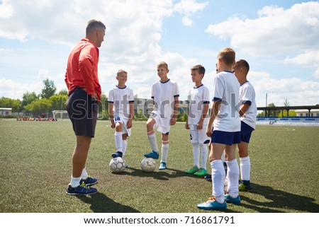 Portrait of junior football team listening to coach giving pep talk before match #716861791