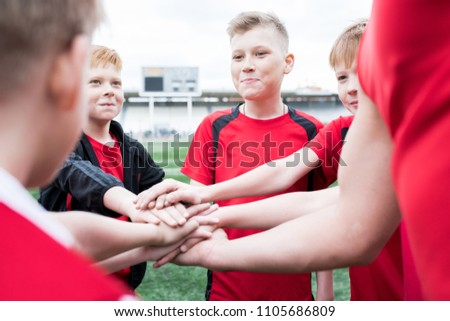 Portrait of junior football team stacking hands during motivational pep talk before match in outdoor stadium, copy space #1105686809