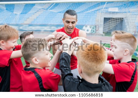 Portrait of junior football team stacking hands during motivational pep talk before match in outdoor stadium, focus on young coach, copy space #1105686818