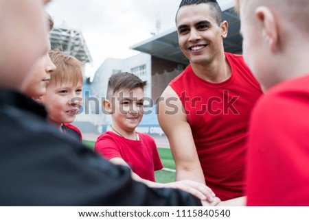 Portrait of junior football team stacking hands during motivational pep talk before match in outdoor stadium, focus on handsome coach, copy space #1115840540