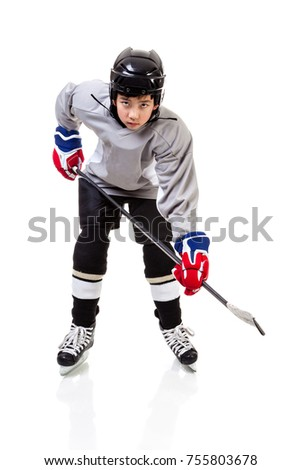 Portrait of junior ice hockey player on the alert with full equipment and uniform posing for a shot with a puck. Isolated on white background. #755803678