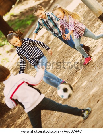 Portrait of junior school girls and boy playing street football #746837449