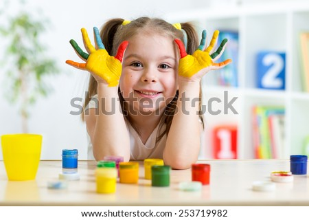 Portrait of kid girl with face and hands painted at home #253719982