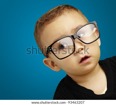 portrait of kid wearing glasses over blue background