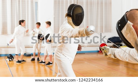 Portrait of kids and adults fencers with trainer engaged in fencing in training room