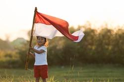 portrait of kids raising indonesian flag in sunset sky