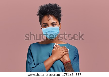 Portrait of kind hearted African American female paramedic wearing a respiratory mask from coronavirus disease, keeps hands on chest, shows her kindness and sympathy, on beige wall. COVID-19 epidemic