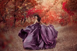 Portrait of Lady in a luxury lush purple dress ,fantastic shot,fairytale princess is walking in the autumn forest,fashionable toning,creative computer colors.  Stylish queen. Red trees October.
