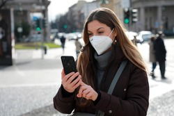 Portrait of lady in winter clothes and FFP2 KN95 face mask walking in city street typing on smartphone