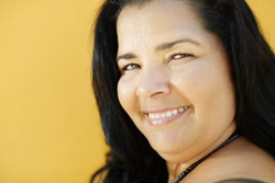 portrait of latin american 50 years old overweight woman smiling on yellow background. Head and shoulders, copy space
