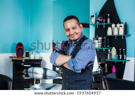 Portrait of latin man barber holding equipments in hand, looking at camera in a barber shop small business in Mexico city Foto stock ©