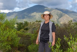 Portrait of latin old farmer woman on the field with shrubbery and mountains in background
