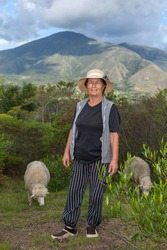 Portrait of latin old shepherd woman on the field with her sheep, shrubbery and mountains in background