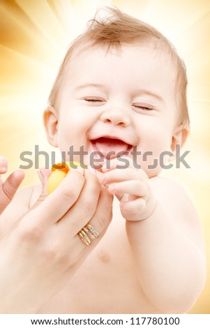 portrait of laughing baby boy in mother hands playing with rubber duck