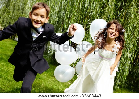 Portrait of laughing children bride and groom with balloons running in park