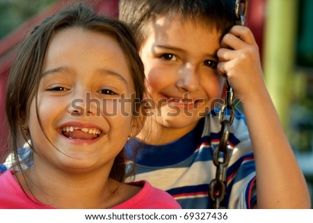 Portrait of laughing children on swing playground outdoors - looking at the camera