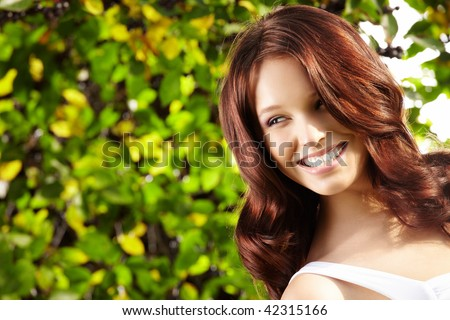 Portrait of laughing curly beauty in a summer garden