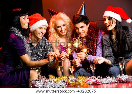 Portrait of laughing friends enjoying xmas lights at new year party