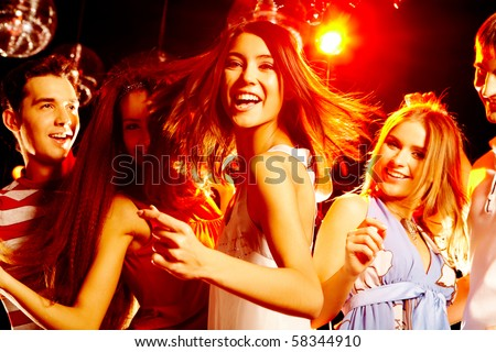 Portrait of laughing girl in white dress dancing among her friends