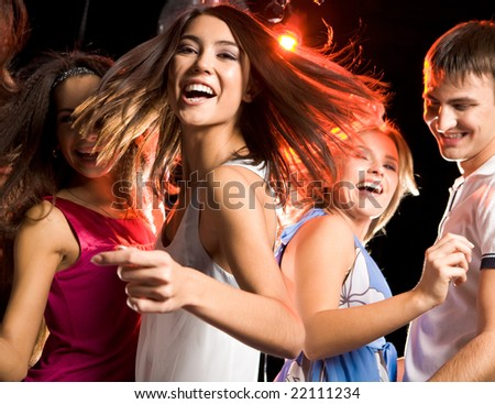 Portrait of laughing girl looking at camera while dancing among her friends at disco