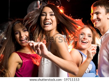 Portrait of laughing girl wearing white dress dancing among her friends