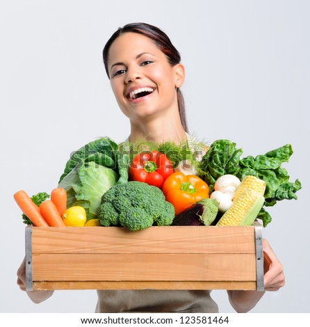 Portrait of laughing happy young woman holding a crate full of fresh organic produce on grey background, promoting healthy living, diet and lifestyle