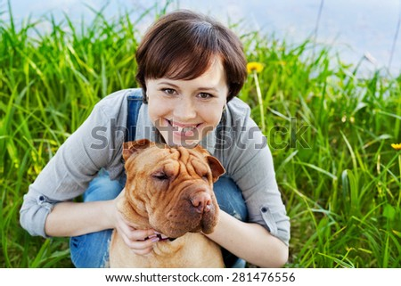 portrait of laughing happy young woman in denim overalls hugging her red cute dog Shar Pei in the green grass in sunny day, true friends forever, people pets concept