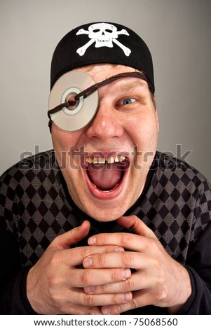 Portrait of laughing information pirate with computer disk on eye