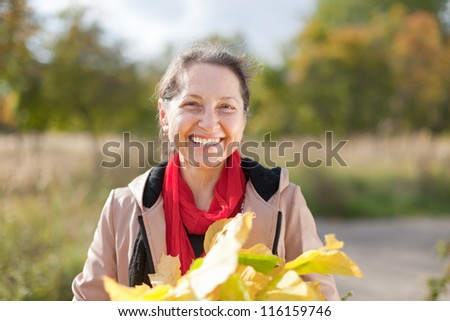 Portrait of  laughing mature woman  in autumn park