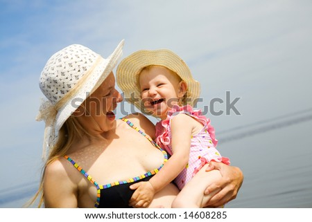 portrait of laughing mother and daughter on the seashore. Focus on the child