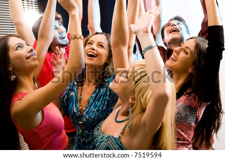 Portrait of laughing people raising their hands