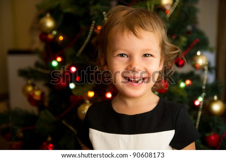 Portrait of laughing toddler girl in front of Christmas tree