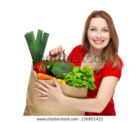 Portrait of laughing young beautiful woman in dress holding grocery shopping bag with healthy vegetarian food