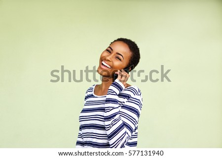 Portrait of laughing young black woman with cellphone against green wall #577131940