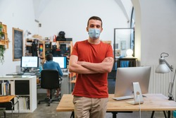 Portrait of leader of a startup in the office with medical mask for protection and prevention contagions from Coronavirus, Covid-19, behind him the other workstations with colleagues at computer