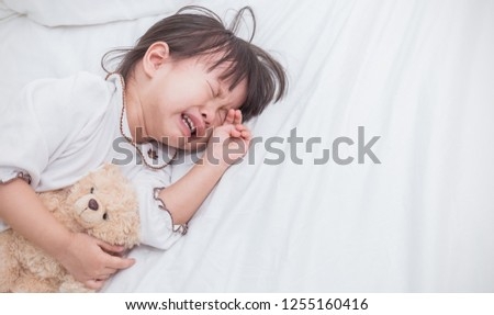 Portrait of little asian crying girl little rolling tears weeping emotion, Closeup young girl hurt in pain crying in white bed copy space. Lonely depress stress angry unhappy terrible two concept